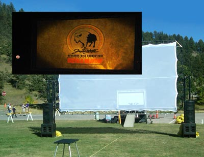 Outdoor Projection screen showing daytime set-up and projection at night